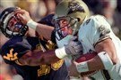 Nick Goings of the Pittsburgh Panthers picks up eight yards while giving the stiff arm to West Virginia's Boo Sensabaugh during 1999's Backyard Brawl.