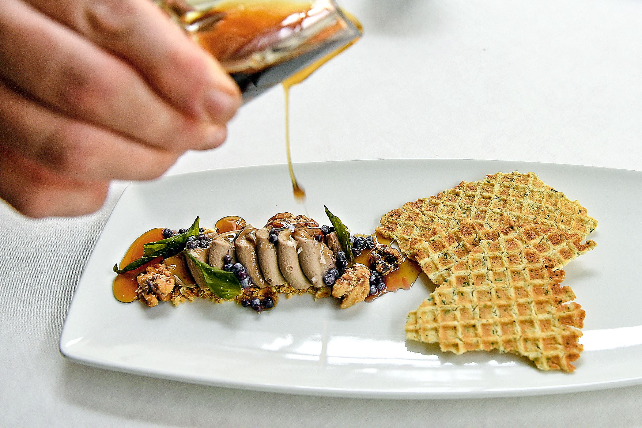 20150910radButterworthMag04-3 Bourbon barrel aged maple syrup drips down on Kristin Butterworth's chicken and waffles served at Lautrec at Nemacolin Woodlands Resort. The dish features chicken liver pate with vanilla scented elderberry, honey walnuts, rosemary waffle, sage and sea salt.