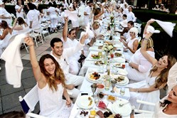 Waving the napkin at the beginning of dinner, are Carolyn Coss, left foreground and clockwise, Adam and Sara DePuglia and Laura Mullin at Diner en Blanc in Gateway Plaza in 2015.