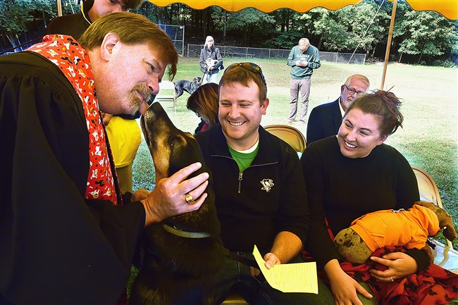 The Rev. Ed Cadwallader gets a lick from Mowgli, a German shepherd mix, as he administers a blessing at an outdoor Sunday worship at the Bradford Woods Community Church in 2015. Owners Matt and Carla Porterfield look on.