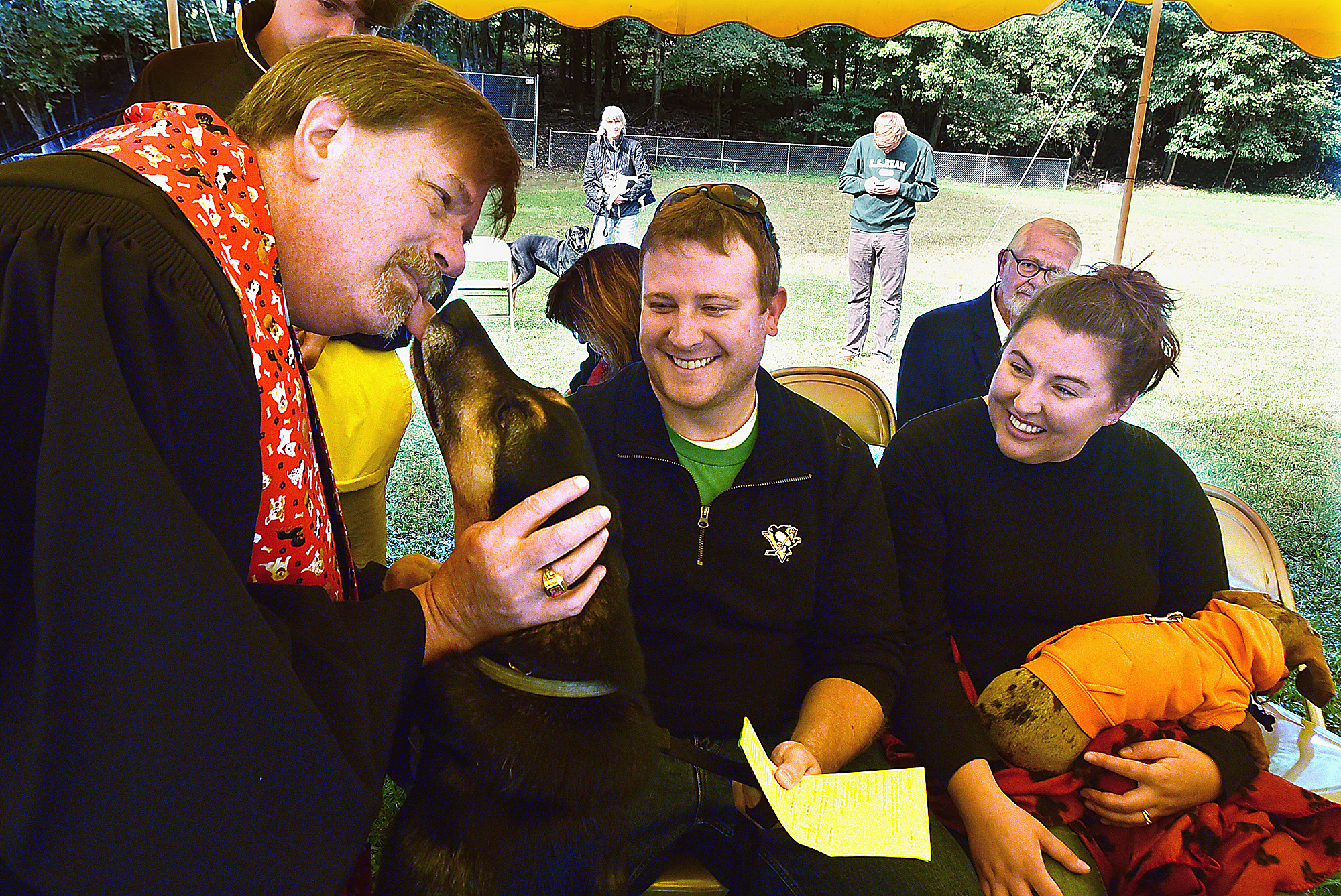 20150913radAnimalBlessWest05-4 The Rev. Ed Cadwallader gets a lick from Mowgli, a German shepherd mix, as he administers a blessing at an outdoor Sunday worship at the Bradford Woods Community Church in 2015. Owners Matt and Carla Porterfield look on.