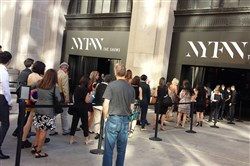 Guests wait in line outside the Skylight at Moynihan Station venue at New York Fashion Week: The Shows to be checked into the building.