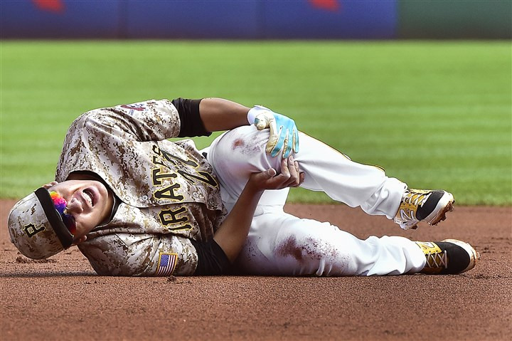 20150917pdPiratesSports01-1 The Pirates' Jung Ho Kang grabs his injured knee after turning a double play against the Cubs on Sept. 17 at PNC Park.