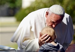 Pope Francis kisses a baby as he parades around the White House Ellipse on Wednesday.