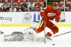 Detroit Red Wings right winger Erik Cole (72) is tripped by Penguins defenseman Rob Scuderi (4) in the first period Thursday night at Joe Louis Arena.