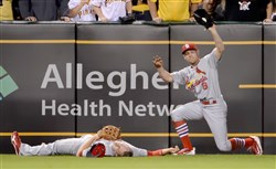 Cardinals' Peter Bourjos holds up the ball after colliding with Stephen Piscotty on a fly ball hit by Pirates' Josh Harrison in the seventh inning Monday at PNC Park.