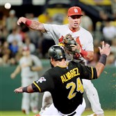 The Pirates' Pedro Alvarez slides to break up a double play against the Cardinals' Kolten Wong in the fourth inning Monday at PNC Park.