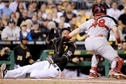 The Cardinals' Tony Cruz tags out Pirates' Starling Marte at home plate in the third inning Monday at PNC Park.