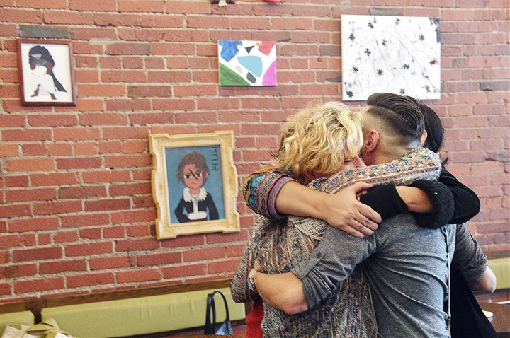 20151001lrhomelessartlocal02-7 Grace Enick, left, an intern with the Homeless Children's Education Fund, hugs volunteers Thursday as they finish hanging the art for display at 21st Street Coffee and Tea in the Strip District.