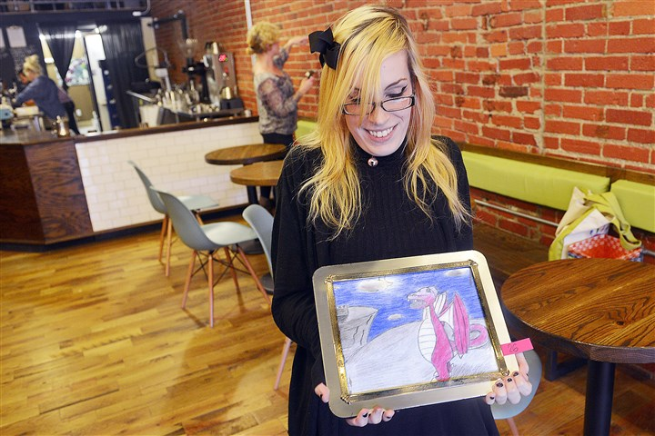 "20151001lrhomelessartlocal01-6 Brittany Meixner of Carrick holds a piece she created that will be displayed at the ""We Live Here"" exhibit tonight at 21st Street Coffee and Tea in the Strip District. She titled the piece ""Dragon in the Night."" Some of the artwork will be accompanied by audio recordings."