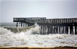 A few hours before high tide, wind-driven waves crash into a fishing pier this weekend in Virginia Beach, Va.