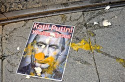 "A picture depicting Russian President Vladimir Putin is splattered with eggs Saturday during a protest in Istanbul against Russian military operations in Syria. The picture reads both in Turkish and Russian: ""Murderer Putin."""