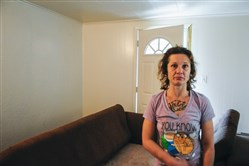 "Kelly Mullen stands in the living room where her friend Jason ""Dirk"" Daniels was shot and his girlfriend was wounded."