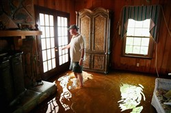 Chad Shields walks through his parent's flooded home Wednesday in Summerville, S.C. The state experienced record rainfall amounts over the weekend and officials expect the damage from the flood to be in the billions of dollars.