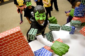 "Dressed as the Hulk, Carley Fair, 10, of Lawrenceville, smashes through a cardboard brick wall during a Super Hero Training Camp, a preview event Wednesday for the upcoming Marvel Universe LIVE! event this weekend at Consol Energy Center. Children at the event were ""taught"" by several actors who will be performing in the show in the ways of the superhero."