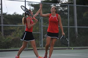 Amanda Nord, left, and Laurel Shymansky of Fox Chapel high-five during the WPIAL AAA girls' tennis championships at North Allegheny High School on Wednesday. They won 6-0, 6-1 against North Allegheny's Tina Li and Ashley Huang.