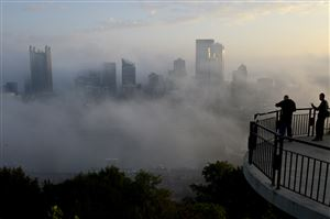 Part of the Pittsburgh skyline rises through the foggy view Thursday from Grandview Avenue on Mount Washington.