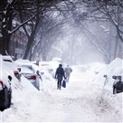 Pedestrians make their way along a snow covered street during a winter snow storm in Cambridge, Massachusetts on Feb. 9, 2015.