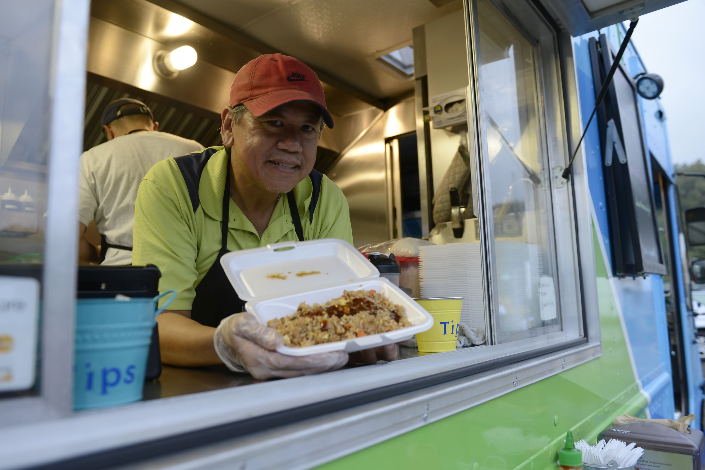 20151009rldFoodTrucks05-4 Jack Jew, owner of the Wok of Life food truck, holds a popular dish, chicken fried rice, at Heidelberg Park in Heidelberg on Friday, October 9, 2015.