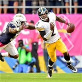 Steelers quarterback Mike Vick breaks away from Chargers linebacker Melvin Ingram in the first quarter Monday night at Qualcomm Stadium in San Diego.