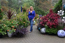 Marie Tuma stands on the sidewalk leading to the front door of her house, surrounded by a few of the many plants she grows in her large garden in Monaca.