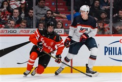 Connor McDavid, of Team Canada, trips over the stick of Brandon Carlo, of Team United States, in a preliminary round game during the 2015 IIHF World Junior Hockey Championships in Montreal December 2014.