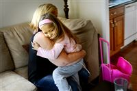 Nan Beachem gets a hug from her daughter, Kyree, 8, at their home Tuesday, October 6 in Ellwood City. The rolling backpack goes everywhere Kyree goes, carrying the medicine she needs to live.