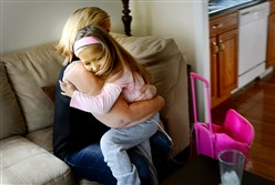Nan Beachem gets a hug from her daughter, Kyree, at their Ellwood City home in October. The rolling backpack, right, goes everywhere Kyree goes, carrying the medicine she needs to live.
