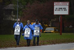 Members of the Peters teachers union walk along East McMurray Road on Oct. 28 in front of the township's middle school.