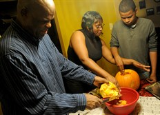 Cornelius and Lasheri Walls of Ross prepare pumpkin seeds Wednesday with their son Cornelius III at their home. The family has regained control of their money thanks to a budgeting system.