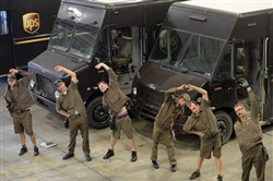 Drivers do light stretching before getting the daily performance update and safety briefing before heading out with the day's deliveries at UPS depot in Jackson, Butler Co.