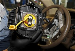 Technician Edward Bonilla holds a recalled Takata airbag inflator after he removed it from a Honda Pilot in June at the AutoNation Honda dealership service department in Miami.