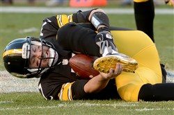 Steelers quarterback Ben Roethlisberger holds his left foot after getting sacked by the Raiders' Aldon Smith in the fourth quarter last Sunday.