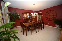 The dark red dining room of the house in Longview Estates in South Fayette has neutral carpeting and window treatments.