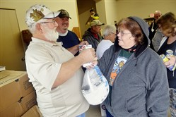 Lynn Lewis, right,  talks Nov. 10 with Ralph Croushore, president of the Peters Creek chapter of the National Wild Turkey Federation, about one of the turkeys he and his organization are distributing through the Central Food Pantry in Elizabeth.