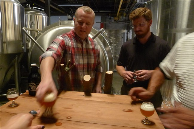 In the former window factory that they're turning into the Levity Brewing Co. in Indiana, Pa., Jay Herman, left, and Luke McKelvy pour samples of their beers. Their other partner is Erich Walls.