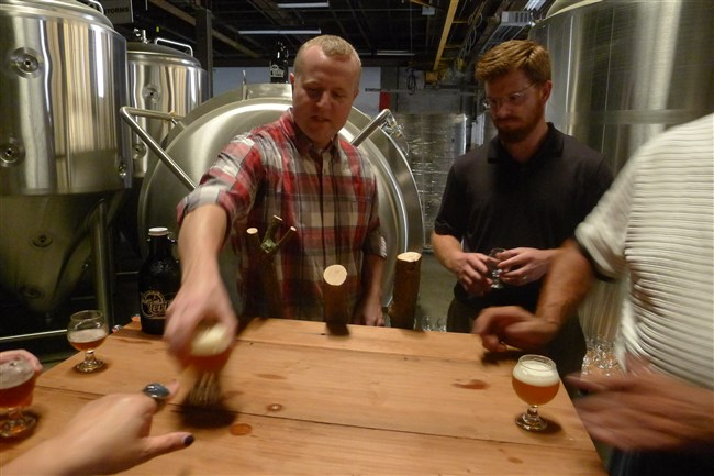 In the former window factory that they've turned into the Levity Brewing Co. in Indiana, Pa., Jay Herman, left, and Luke McKelvy pour samples of their beers back in November. Their other partner is Erich Walls. The brewpub opened Friday night.