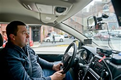 "Andriy Bohdan drives his Cranberry Taxi while looking for airport fares at hotels in Downtown Pittsburgh. ""I've gotten better, doing more driving,"" he says about learning routes."