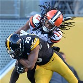 Steelers safety Mike Mitchell intercepts a pass in front of Browns receiver Travis Benjamin in the fourth quarter Sunday at Heinz Field.