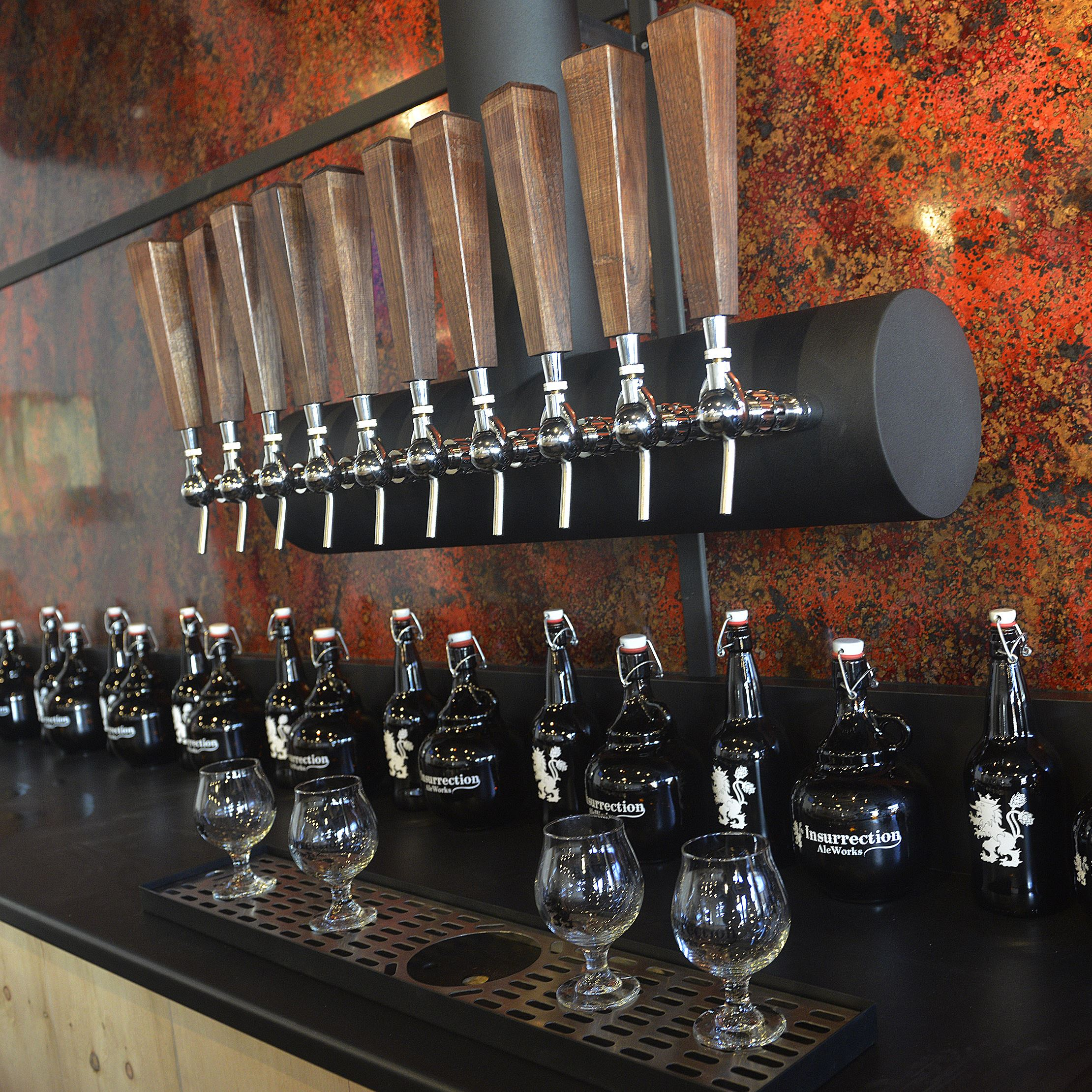 20151115lrinsurrectionmag02-8 Growlers and glasses sit on the back bar at Insurrection AleWorks.