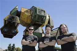 In this photo taken Friday, Oct. 9, 2015, MegaBots founders from left, Brinkley Warren, Matt Oehrlein and Gui Cavalcanti stand below their 15-foot tall, piloted Mk.II robot at the Pioneer Summit in Redwood City, Calif. Let the giant robot wars begin. A team of American engineers challenged a group in Japan to a battle for robot supremacy, and the Japanese said bring it on. So Oakland-based MegaBots has launched a Kickstarter campaign to raise money to turn the Mk.II, into a real fighting machine, ready for hand-to-hand combat. (AP Photo/Eric Risberg)