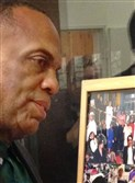 The Rev. Glenn Grayson with a collage of photographs at Hill District pop-up museum.
