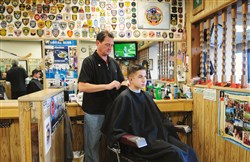 J.R. Hoffman gives Mitchell Grunwald, 16, a haircut in Mr. Hoffman's barber shop, the Great Southern Barber Shop, in Bridgeville. The barber shop