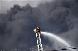 Firefighters face the smoke of the multi-alarm fire Tuesday at the Leetsdale Industrial Park.