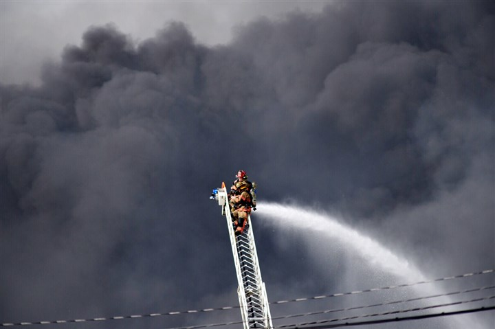 Bob-Donaldson-1447782357 Firefighters face the smoke of the multi-alarm fire Tuesday at the Leetsdale Industrial Park.