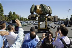 People watch the MegaBots 15-foot tall, piloted Mark II robot in action at the Pioneer Summit in Redwood City, Calif.