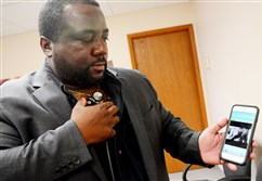 Rijuven Corp. CEO Evens Augustin demonstrates how to operate a CardioSleeve on a mobile phone. The device monitors and records a patient's heartbeat and EKG.