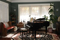 The front parlor contains a piano and other musical instruments. On the left is an old church pew.