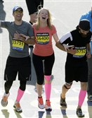 Timothy Haslet, left, and David Haslet, right, celebrate with their sister Adrianne Haslet-Davis as she crosses the finish line of the 118th Boston Marathon in Boston in April 2014.