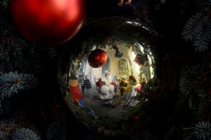 Santa Claus is reflected on an ornament during the Light Up Night ceremony at the City-County Building, Downtown, on Friday.